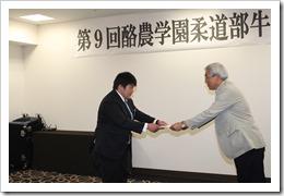 飯田進作会長より本間主将に目録が手渡される。